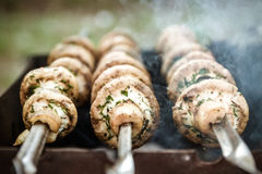 Grilled mushrooms on skewers cooked in a brazier, close-up, retr Royalty Free Stock Images