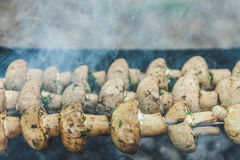 Grilled mushrooms on skewers cooked in a brazier, close-up, retr Stock Photography