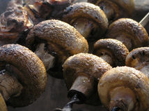 Grilled mushrooms. Mushrooms strung on a skewer and roasting on the grill Stock Photos