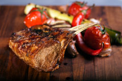 Grilled mutton chops on cutting board. Side of lamb with pepper on a butcher block royalty free stock photography