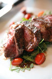 Grilled New York Strip on a bed of Arugula. Grilled New York Strip steak on a bed of arugula (rocket) with sliced pear tomatoes royalty free stock photos
