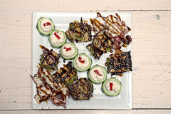 Grilled octopus with backed squash on square dish. Grilled octopus with backed squash, cucumber and balsamic sauce served on square dish on wooden table royalty free stock photography