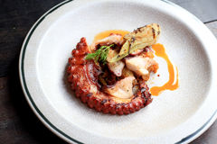 Grilled octopus tentacles with lemon and parsley leaves on dish. royalty free stock images