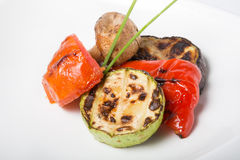 Grilled oily vegetables. Served on a white plate Stock Photos