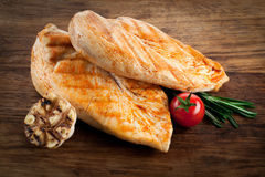 Grilled organic chicken with tomato and garlic on wood Stock Images