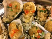 Grilled oyster seafood Chinese cuisine food. Roasted oysters with spices in restaurant in China Asia. Grilled fresh seafood. Exotic traditional Chinese cuisine Stock Images