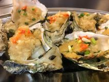 Grilled oyster seafood Chinese cuisine food. Roasted oysters with spices in restaurant in China Asia. Grilled fresh seafood. Exotic traditional Chinese cuisine Royalty Free Stock Photos