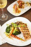 Grilled Pacific Coast salmon with grilled vegetables. Grilled Pacific Coast salmon and vegetables with shrimp and a glass of chardonnay Royalty Free Stock Images