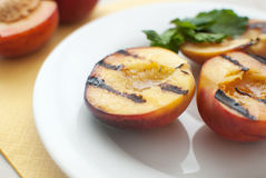 Grilled peaches dessert. With leaf of mint Stock Photo