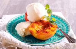 Grilled peaches and ice cream dessert. Over blue plate Stock Image