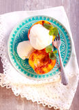 Grilled peaches and ice cream dessert. Over blue plate Royalty Free Stock Images