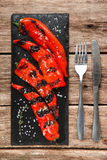 Grilled pepper. Appetizing bright vegetarian food. Delicious and juicy grilled paprika served on black slate with knife and fork, on rustic wooden table, top Royalty Free Stock Photography