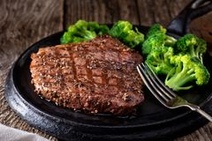 Grilled Pepper Steak. A delicious grilled pepper steak with broccoli on a rustic wooden table stock images