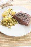 Grilled pepper steak with potato and pea Stock Image