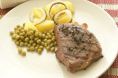 Grilled pepper steak with potato and pea Royalty Free Stock Photo