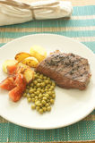 Grilled pepper steak with roasted potato and pea Royalty Free Stock Photography