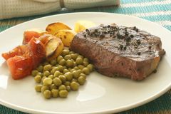 Grilled pepper steak with roasted potato and pea Stock Images