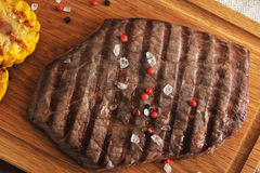 Grilled piece of beef with a crystalline salt, pepper and grille. D corn on a wooden Board - top view Royalty Free Stock Photo