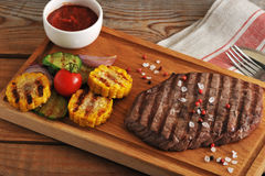 Grilled piece of beef with a crystalline salt, pepper and grille. D corn, zucchini, onion  on a wooden Board - top view Royalty Free Stock Images