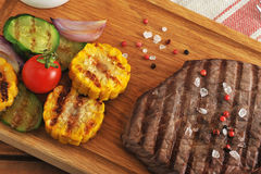 Grilled piece of beef with a crystalline salt, pepper and grille. D corn, zucchini, onion  on a wooden Board - top view Royalty Free Stock Photo