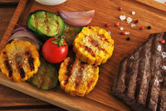 Grilled piece of beef with a crystalline salt, pepper and grille. D corn, zucchini, onion  on a wooden Board - top view Stock Photos