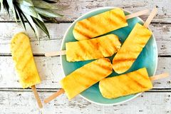 Grilled pineapple wedges against rustic white wood Royalty Free Stock Photos