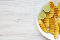Grilled pineapple wedges with lime on white plate over white wooden surface, top view. Summer food. Idea for snack. stock image