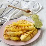 Grilled pineapple wedges on a pink plate with honey and lime over white wooden surface, side view. Summer food stock photography