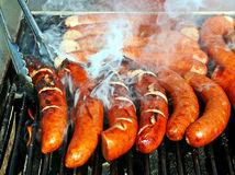 Grilled Polish Sausage. Known by various names worldwide, being prepared at a local Food Festival stock photo