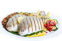 Grilled Pompano. Fish with wild rice ,vegetables and oysters on a white background Stock Image