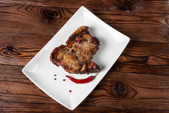 Grilled pork barbecue. Pork steak grilled with spicy peppers and cranberry sauce on a wooden background Stock Image