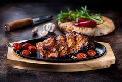 Grilled pork BBQ ribs. Serving on a cast-iron frying pan stock images