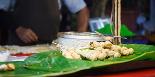 Grilled Pork and Beef Meat Ball Sticks and dipping sauce pot placed on green banana leaf shelf in street food market stall. Traditional fast food menu served royalty free stock image