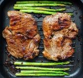 Grilled pork chop with asparagus Stock Photos