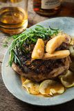 Grilled pork chop with bourbon spiced maple apples served with r Royalty Free Stock Image