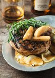 Grilled pork chop with bourbon spiced maple apples served with r Stock Images