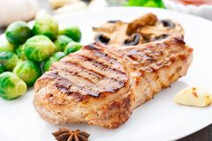 Grilled pork chop with brussels sprouts Stock Photos