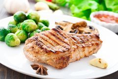 Grilled pork chop with brussels sprouts Royalty Free Stock Image