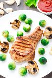 Grilled pork chop with brussels sprouts Stock Image