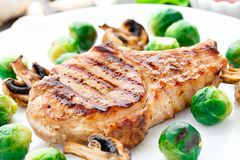 Grilled pork chop with brussels sprouts Royalty Free Stock Images
