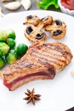 Grilled pork chop with brussels sprouts Royalty Free Stock Photos