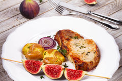 Grilled Pork Chop with Figs on Scewer, Crisp Roasted Potatoes and Thyme. Royalty Free Stock Photography