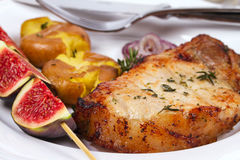 Grilled Pork Chop with Figs on Scewer, Crisp Roasted Potatoes and Thyme. Stock Photos