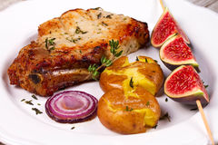 Grilled Pork Chop with Figs on Scewer, Crisp Roasted Potatoes and Thyme. Stock Photo