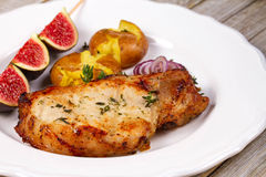 Grilled Pork Chop with Figs on Scewer, Crisp Roasted Potatoes and Thyme. Stock Photography