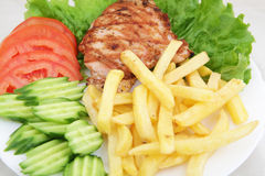 Grilled pork chop with french fries. Cucumber and tomatoes royalty free stock images