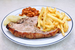 Grilled pork chop fries beans and sauce Royalty Free Stock Images