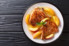 Grilled pork chop with glazed peaches and honey garlic sauce close-up on a plate. horizontal top view from above. Grilled pork chop with glazed peaches and honey stock images