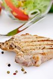 Grilled pork chop, peppercorns, meat fork Royalty Free Stock Image