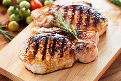 Grilled pork chop with rosemary leaf on wooden board Royalty Free Stock Photography